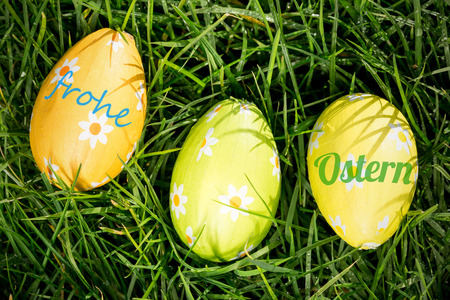 Ostern: frohe ostern against three easter eggs nestled in the grass