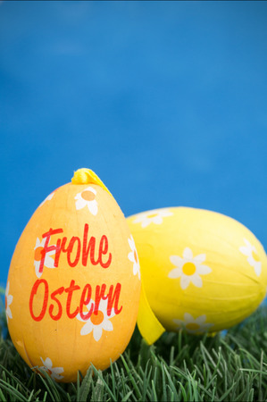 Ostern: frohe ostern against two easter eggs on grass Stock Photo