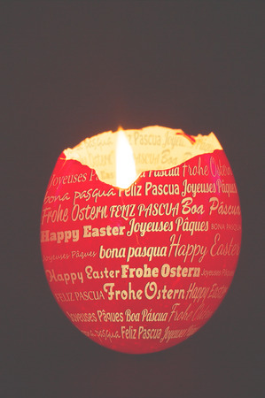 candle holder: Happy easter in different languages against red egg shell used as a candle holder Stock Photo