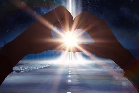 leading light: Woman making heart shape with hands against road leading out to the horizon with light beam