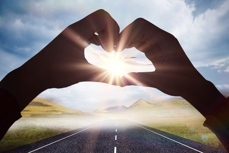 taking off: Woman making heart shape with hands against 3d plane taking off over street Stock Photo