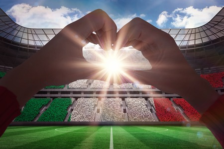 Woman making heart shape with hands against stadium full of italy football fans