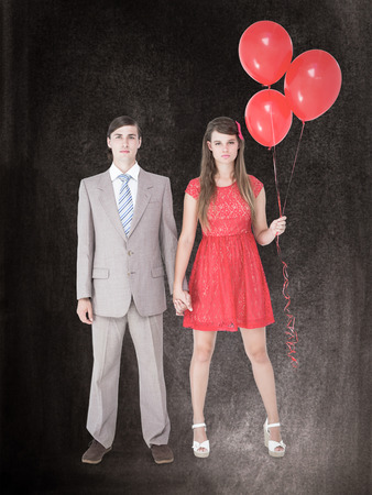 together with long tie: Unsmiling geeky couple standing hand in hand against black background