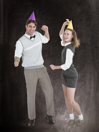 computer dancing: Geeky couple dancing with party hat  against black background Stock Photo