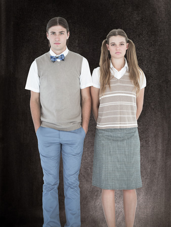unsmiling: Unsmiling geeky hipsters looking at camera  against black background