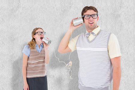 tin can phone: Geeky hipster couple speaking with tin can phone  against white background Stock Photo