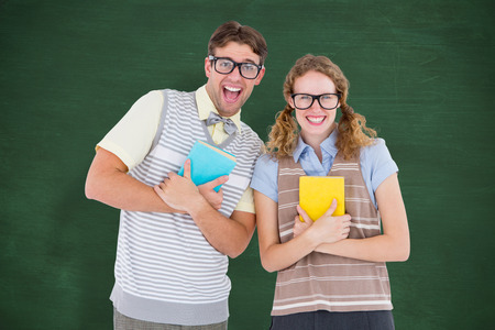 cheesy grin: geeky hipster couple holding books and smiling at camera  against green chalkboard Stock Photo