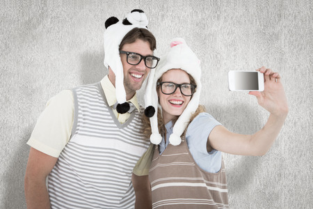 Geeky hipster couple taking selfie with smartphone against white background photo
