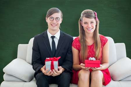 Cute geeky couple smiling and holding gift  against green chalkboard photo
