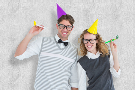cheesy grin: Geeky couple with party hat and party horn against white background