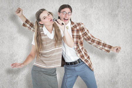 together with long tie: Happy geeky hipsters singing with microphone against white background