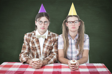 together with long tie: Unsmiling geeky hipsters celebrating birthday  against green chalkboard