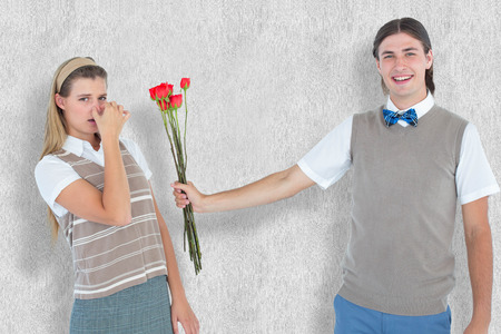 Geeky hipster offering red roses to his girlfriend  against white background photo