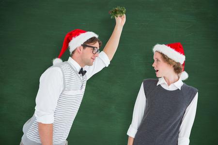 mistletoe: Geeky hipster holding mistletoe  against green chalkboard