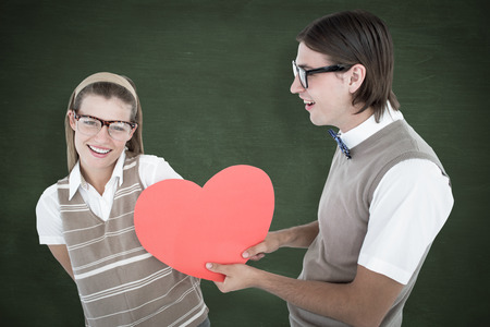 Geeky hipster offering red heart to his girlfriend  against green chalkboard photo