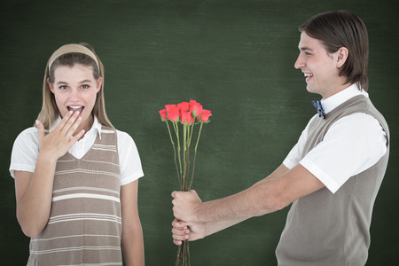 Geeky hipster offering red roses to his girlfriend  against green chalkboard photo