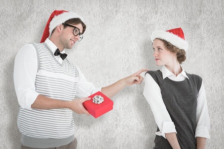 Geeky hipster offering present to his girlfriend against white background photo