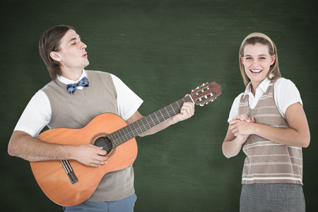 serenading: Geeky hipster serenading his girlfriend with guitar  against green chalkboard