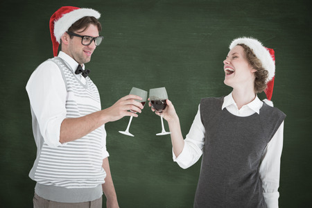 Happy geeky hipster couple drinking red wine against green chalkboard photo