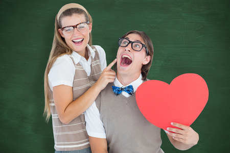 Excited geeky hipster and his girlfriend  against green chalkboard photo