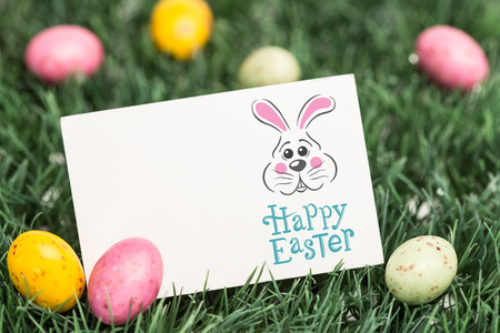 laying egg: easter bunny with greeting against blank greeting card with easter eggs Stock Photo