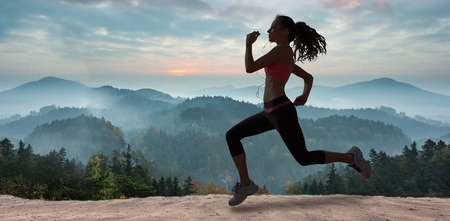 range of motion: Full length of healthy woman jogging  against misty landscape Stock Photo
