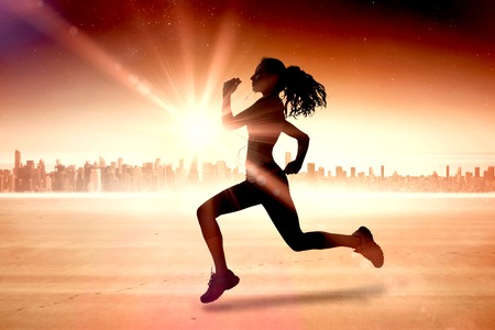 body concern: Full length of healthy woman jogging  against sun shining over city Stock Photo