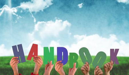 handbook: Hands holding up handbook against blue sky over green field