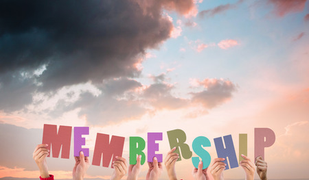 membership: Hands holding up membership against orange and blue sky with clouds