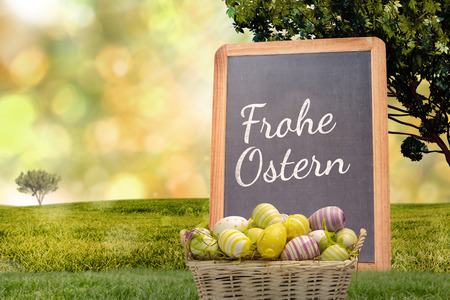 Ostern: Easter eggs in basket against frohe ostern Stock Photo