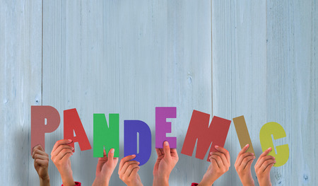 pandemic: Hands holding up pandemic against wooden planks Stock Photo