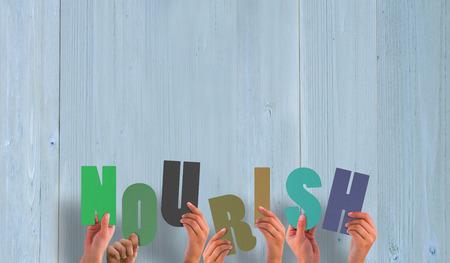 nourish: Hands holding up nourish against wooden planks