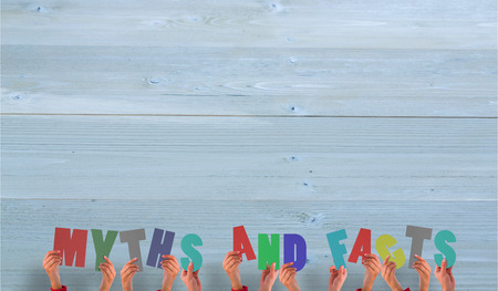 myths: Hands holding up myths and facts against bleached wooden planks background