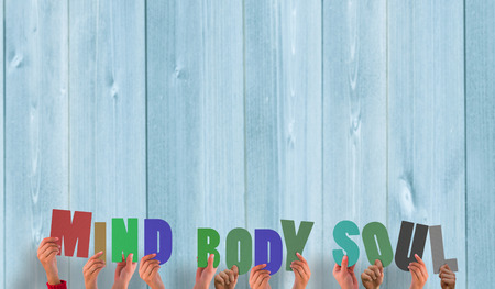 mind body soul: Hands holding up mind body soul against wooden planks