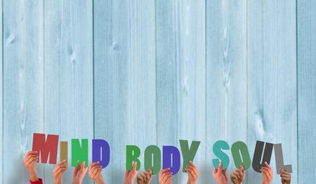 mind body soul: Mani che tengono fino anima corpo mente contro tavole di legno
