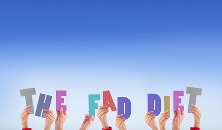 fad: Hands holding up the fad diet against bright blue sky Stock Photo