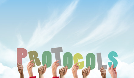 protocols: Hands holding up protocols against blue sky Stock Photo