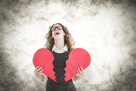 Geeky hipster holding a broken heart card against grey background photo