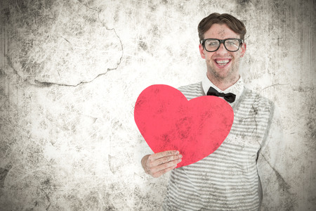 cheesy grin: Geeky hipster holding heart card against grey background