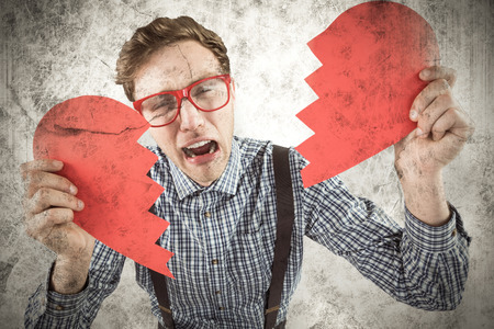 broken love: Geeky hipster holding a broken heart  against grey background Stock Photo