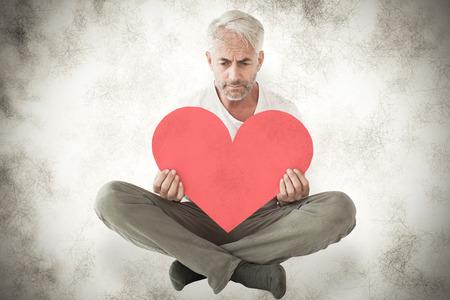 desolaci�n: Malestar hombre sentado la celebraci�n de la forma del coraz�n contra el fondo gris