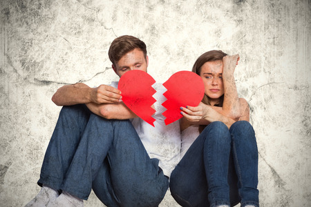 Young couple holding broken heart against grey background 스톡 콘텐츠