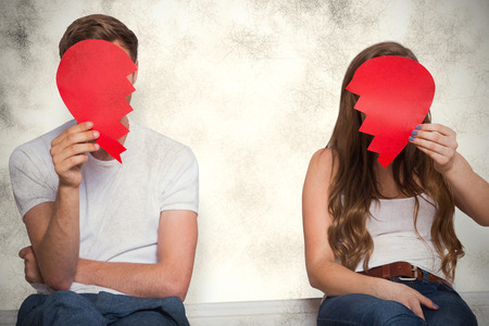quarrel: Couple holding broken heart against grey background Stock Photo