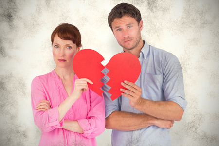 Couple holding a broken heart against grey background photo