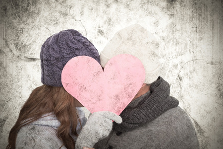 warm clothing: Couple in warm clothing holding heart against grey background Stock Photo