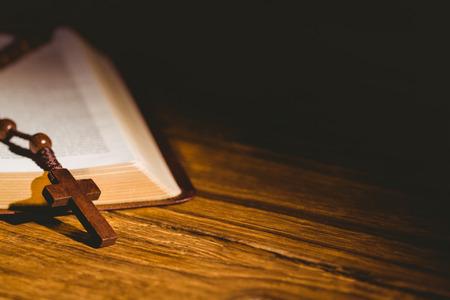 木製テーブルの上のロザリオ ビーズと開く聖書