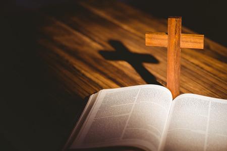 vangelo aperto: Apra la bibbia con l'icona crocifisso dietro su tavola di legno