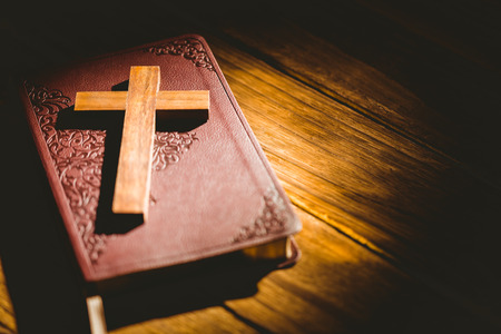 jehovah: Crucifix icon resting on the bible on wooden table Stock Photo