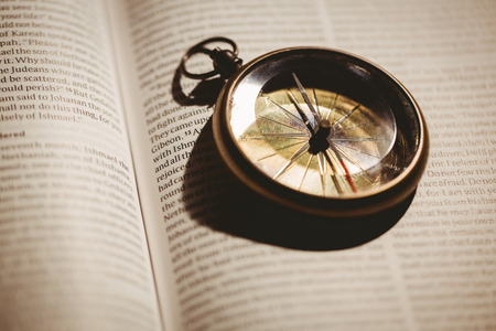 jehovah: Close up of compass on open bible Stock Photo