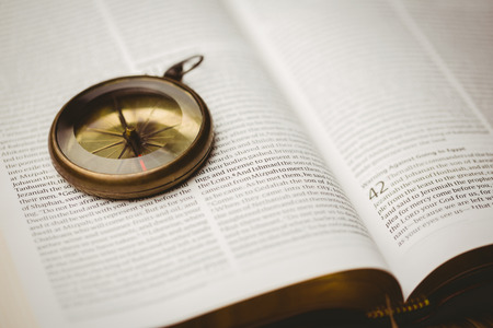 methodist: Close up of compass on open bible Stock Photo
